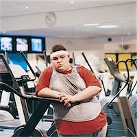 fat man exercising - Fat Man Leaning Against a Running Machine Stock Photo - Premium Royalty-Freenull, Code: 6106-07002451