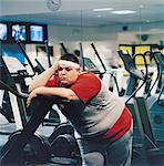 Fat Man Leaning Against a Running Machine