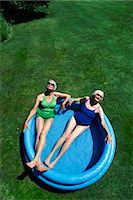 View Directly Above of Two Senior Women Lying in a Paddling Pool, Wearing Swimsuits Stock Photo - Premium Royalty-Freenull, Code: 6106-07002674