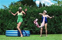 Two Senior Women Wearing Swimsuits, Dancing on the Grass in Front of a Paddling Pool Stock Photo - Premium Royalty-Freenull, Code: 6106-07002675