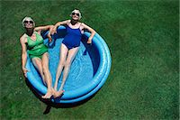 Above View of Two Elderly Women Relaxing in a Paddling Pool on a Garden Lawn Stock Photo - Premium Royalty-Freenull, Code: 6106-07002680