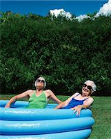 Two Elderly Women Sitting in a Padlling Pool in Summer on a Garden Lawn Stock Photo - Premium Royalty-Freenull, Code: 6106-07002682