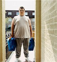 fat man full body - Overweight Man Stands at a Doorway Holding Carrier Bags of Groceries Stock Photo - Premium Royalty-Freenull, Code: 6106-07002763