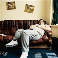 fat man full body - Overweight Young Man Falls Asleep While Lying on a Sofa Watching TV Stock Photo - Premium Royalty-Freenull, Code: 6106-07002765