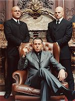 Wealthy Criminal Sitting in an Armchair Between two Bodyguards Stock Photo - Premium Royalty-Freenull, Code: 6106-07002846