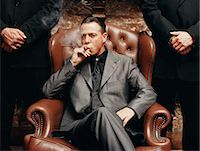 Wealthy Criminal Sitting in an Armchair Between two Bodyguards Stock Photo - Premium Royalty-Freenull, Code: 6106-07002847