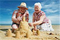 Elderly Couple Kneeling on a Beach Building a Sandcastle Stock Photo - Premium Royalty-Freenull, Code: 6106-07002861