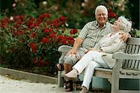 people sitting on bench - A Senior Couple Sitting on a Park Bench Next to Rose Bushes Stock Photo - Premium Royalty-Freenull, Code: 6106-07003351