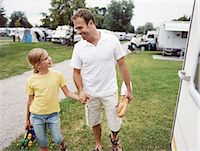 Father and Daughter Walking Hand in Hand Back to Their Caravan on a Campsite Stock Photo - Premium Royalty-Freenull, Code: 6106-07003420