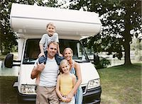 Couple Standing With Their Son and Daughter in Front of Their Mobile Home by a Lake Stock Photo - Premium Royalty-Freenull, Code: 6106-07003444