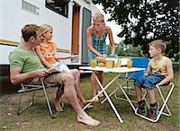 Family on Vacation, Sitting Around a Table Next to Their Motor Home and Having Lunch Stock Photo - Premium Royalty-Freenull, Code: 6106-07003450