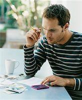savings - Serious Looking Man Examining a Bill Stock Photo - Premium Royalty-Freenull, Code: 6106-07004606