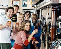 Six Friends Standing at a Counter of a Pub Toasting Drinks Stock Photo - Premium Royalty-Freenull, Code: 6106-07004724