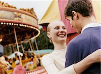 Teenage Couple Stand in a Fairground Laughing and Embracing Stock Photo - Premium Royalty-Freenull, Code: 6106-07004798