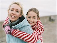 Portrait of a Mother Giving Her Daughter a Piggyback, With both Wearing Warm Clothing Stock Photo - Premium Royalty-Freenull, Code: 6106-07005027
