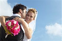 Newlywed Groom Kisses a Bride Holding a Bouquet on Her Cheek Stock Photo - Premium Royalty-Freenull, Code: 6106-07005189