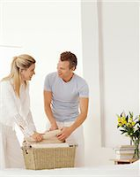 Couple Stand in Their Bedroom Helping Each Other Unpack a Laundry Basket Stock Photo - Premium Royalty-Freenull, Code: 6106-07005298