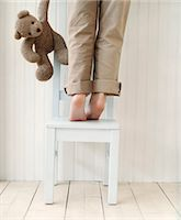 Low Section Rear View of a Child Standing Tip-Toe on a Chair by a Wall, a Teddy Bear Hanging by Their Side Stock Photo - Premium Royalty-Freenull, Code: 6106-07005313