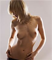 Half Dressed Woman Standing With Her Hands on Her Hips Stock Photo - Premium Royalty-Freenull, Code: 6106-07005448