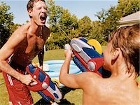Son Fires a Water-Gun in His Fathers Face Beside a Paddling Pool in a Garden Stock Photo - Premium Royalty-Freenull, Code: 6106-07005583
