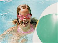 Smiling Young Girl Wearing Pink Swimming Goggles in a Swimming Pool Stock Photo - Premium Royalty-Freenull, Code: 6106-07005592