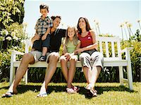 Family of Four Sit on a Park Bench in Summer Sunlight Together Stock Photo - Premium Royalty-Freenull, Code: 6106-07005601