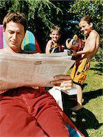 Man Sits Reading a Newspaper Unaware of Two Boys Aiming Water-Guns at Him Stock Photo - Premium Royalty-Freenull, Code: 6106-07005606