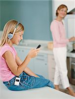 preteen touch - Young Girl Sits on a Kitchen Counter Texting on Her Mobile Phone and Listening to Her MP3 Player Stock Photo - Premium Royalty-Freenull, Code: 6106-07005621