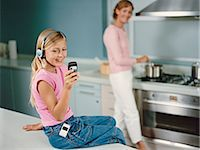 preteen touch - Young Girl Sits on a Kitchen Counter Texting on Her Mobile Phone and Listening to Her MP3 Player Stock Photo - Premium Royalty-Freenull, Code: 6106-07005625