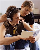 Two Twenty something Men in a Bedroom Reading From a CD Case Stock Photo - Premium Royalty-Freenull, Code: 6106-07005708