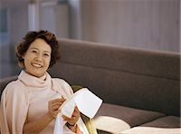 Senior Woman Sitting in Living Room Embroidering Stock Photo - Premium Royalty-Freenull, Code: 6106-07005803