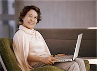 Senior Woman Sitting With a Laptop on Her Lap Stock Photo - Premium Royalty-Freenull, Code: 6106-07005807