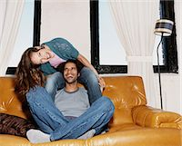Couple Mucking About Together and Laughing on a Leather Sofa Stock Photo - Premium Royalty-Freenull, Code: 6106-07005826