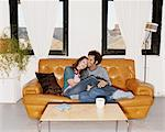 Couple Sat Together on a Leather Sofa Stock Photo - Premium Royalty-Freenull, Code: 6106-07005831