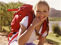 preteen girl pigtails - Portrait of a Girl Outdoors, Crouching Wearing a Rucksack Stock Photo - Premium Royalty-Freenull, Code: 6106-07006003