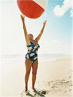 Senior Woman Standing on a Beach Reaching for a Beach Ball Stock Photo - Premium Royalty-Freenull, Code: 6106-07006018