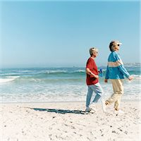 Two Mature Women Power walking on a Sandy Beach at the Water's Edge Stock Photo - Premium Royalty-Freenull, Code: 6106-07006115