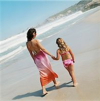 Mother Walking With Her Child Hand in Hand Along a Beach Stock Photo - Premium Royalty-Freenull, Code: 6106-07006157