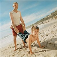 preteen touch - Father Giving a Wheelbarrow to His Son on a Beach Stock Photo - Premium Royalty-Freenull, Code: 6106-07006159