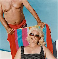 Senior Woman Lying on a Sun Lounger with an Unrecognizable Man Standing Behind Her Stock Photo - Premium Royalty-Freenull, Code: 6106-07006197