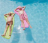 Two Senior Men Lying on Airbeds in a Swimming Pool Stock Photo - Premium Royalty-Free, Artist: Mint Images, Code: 6106-07006201