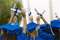 Group of Graduates Dressed in Graduation Gowns Holding Scrolls in the Air Stock Photo - Premium Royalty-Freenull, Code: 6106-07006698