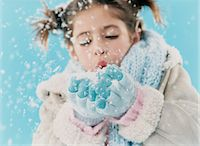Young Girl Wearing Warm Clothing and Blowing a Handful of Snow Stock Photo - Premium Royalty-Freenull, Code: 6106-07006954