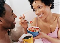 Thirty-something Couple Sitting on a Bed, Woman Feeding Her Partner Breakfast Cereal Stock Photo - Premium Royalty-Freenull, Code: 6106-07006959