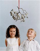 Portrait of a Young, Well-Dressed Boy and Girl Standing Under Mistletoe, the Boy Looking Upwards Stock Photo - Premium Royalty-Freenull, Code: 6106-07007030