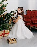 Young Girl in a Dress Hangs Christmas Ornaments on a Christmas Tree in Her Living Room Stock Photo - Premium Royalty-Freenull, Code: 6106-07007031