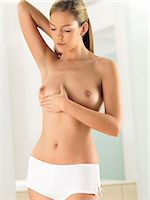 Woman Examining Her Breast in a Bathroom Stock Photo - Premium Royalty-Freenull, Code: 6106-07007318
