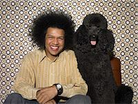 represented - Man With an Afro Sitting Next to a Black Poodle Stock Photo - Premium Royalty-Freenull, Code: 6106-07007392