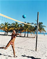 slim - Young Woman in a Bikini Throws a Volleyball Over a Net on the Beach Stock Photo - Premium Royalty-Freenull, Code: 6106-07008047
