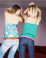 Rear View of Two Young Women Dancing Side by Side, in Unison Stock Photo - Premium Royalty-Freenull, Code: 6106-07008078